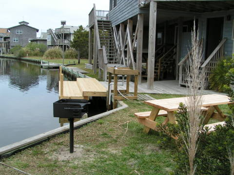 Picnic table, grill, and fish cleaning table by the dock